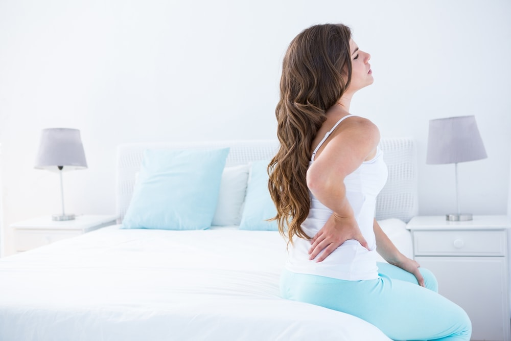 woman on mattress with lower back pain